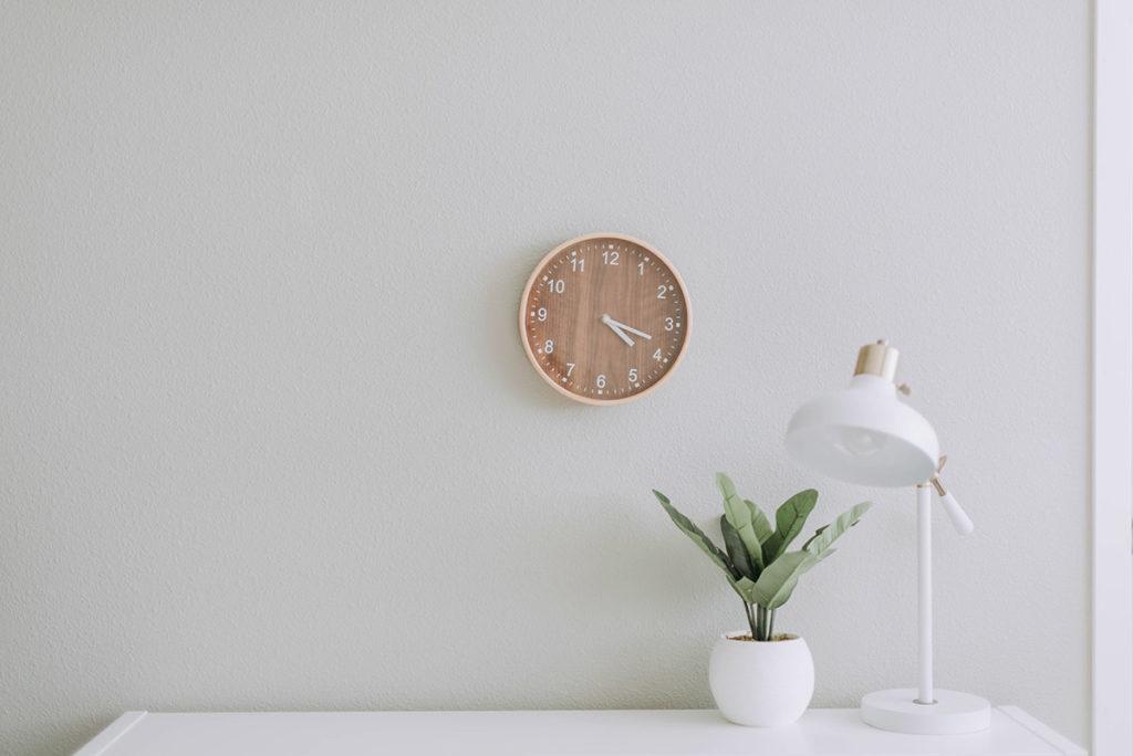 Man sieht eine weisse Wand mit einer Uhr, davor ein weisser Tisch mit einer Pflanze und einer Lampe darauf.