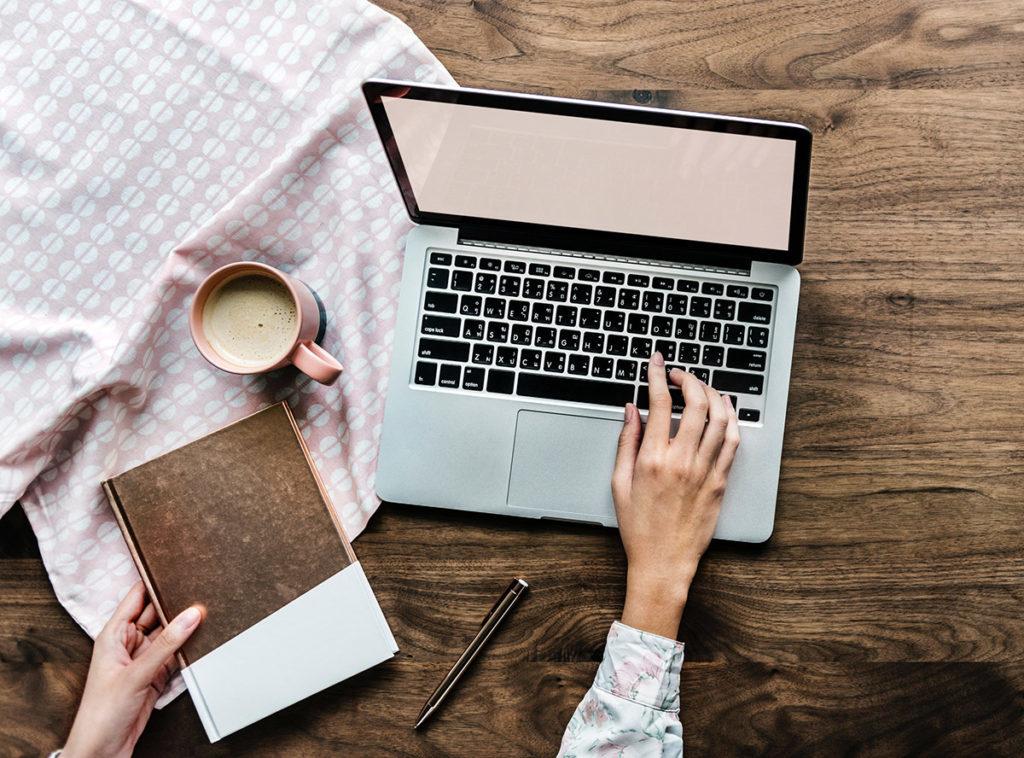 Man sieht einen Laptop von oben. Eine Frau hat ihre rechte Hand darauf gelegt, in der linken hält sie ein Notizbuch, vor dem eine Kaffeetasse steht. Zwischen dem Notizbuch und der rechten Hand liegt ein Kugelschreiber.