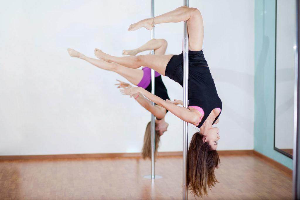 Zwei junge Frauen betreiben kopfüber Polefitness für gesunde Beine.