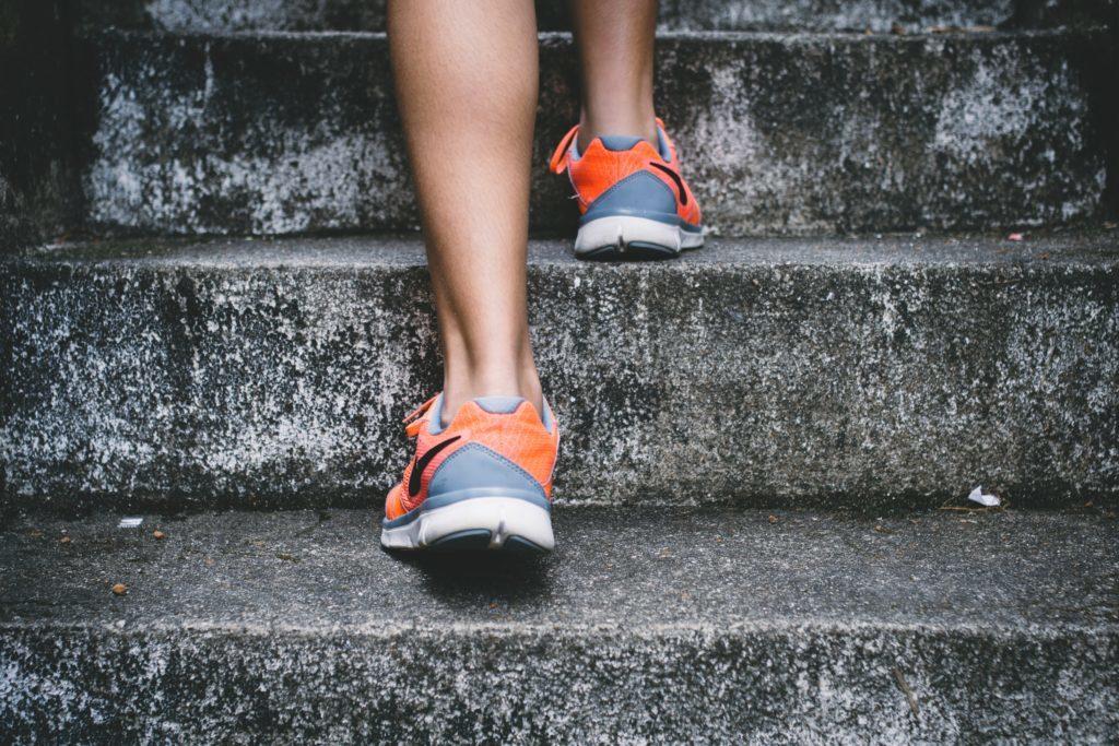 Eine Frau mit Turnschuhen läuft eine Treppe hoch.